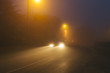 Country asphalt road in the region of Normandy, France in foggy day. Street lamps and car headlights at night. Toned