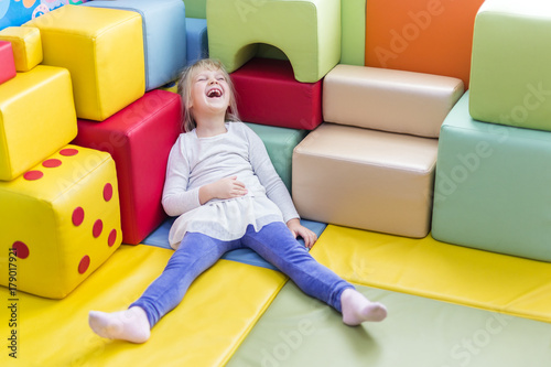 Fotografía  Little cute caucasian blond girl die laughing while playing with soft building b