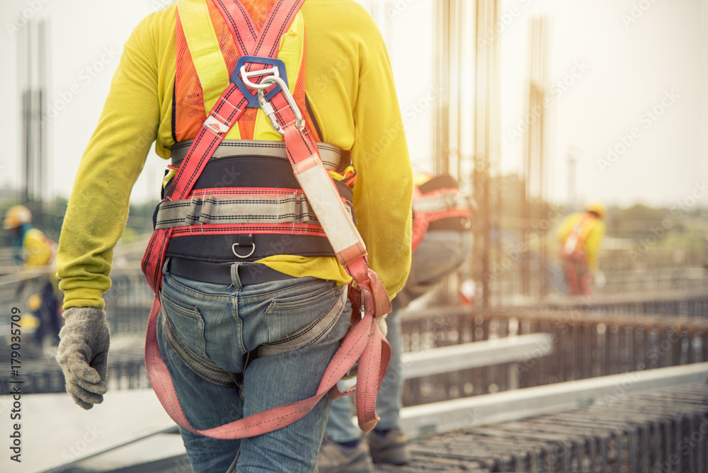 Fototapety, obrazy: Working at height equipment. Fall arrestor device for worker with hooks for safety body harness on selective focus. Worker as a background.