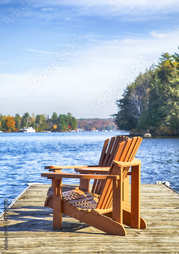 Canvas Print Two Muskoka chairs on a wood dock at a blue lake