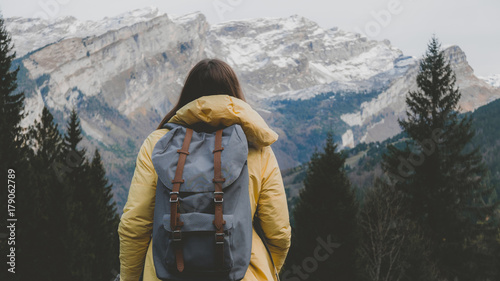Young Caucasian female hiker in yellow raincoat wearing backpack enjoys the moun Canvas Print