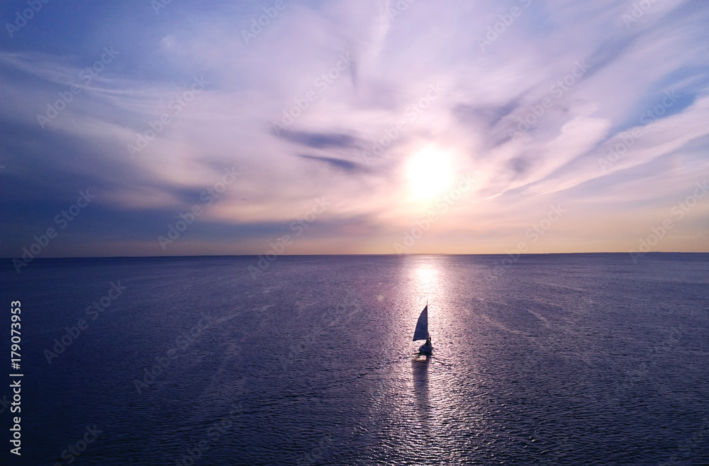Fototapeta Romantic frame: yacht floating away into the distance towards the horizon in the rays of the setting sun. Purple-pink sunset
