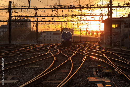 A train on the railroad tracks  during sunrise Fototapeta