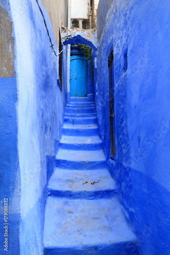 Deurstickers Smal steegje Blue door at the end of a narrow alley with steps, in Chaouen, Morocco