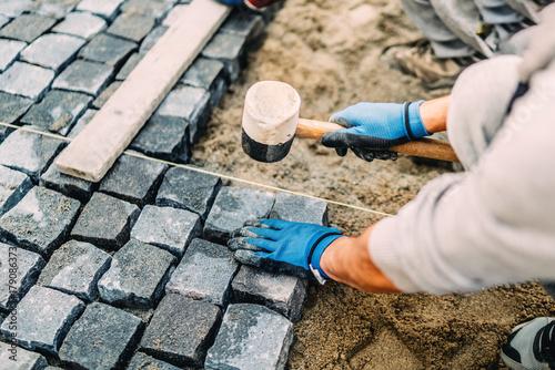 Fototapeta Construction worker installing stone on pavement. Details of construction site obraz