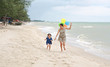 Mother and child girl running on the beach with colorful balloons. Holiday concept.