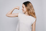 confident young sporty Caucasian woman in a white t-shirt showing biceps against white background