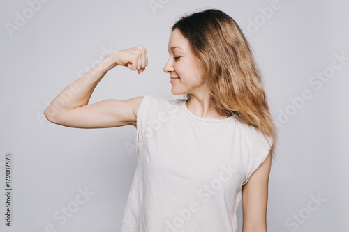 Foto confident young sporty Caucasian woman in a white t-shirt showing biceps against