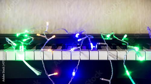 Obraz na płótnie Bożenarodzeniowa girlanda z światłami na elektronicznym pianinie - dekoracja dla świętowania boże narodzenia i nowy rok