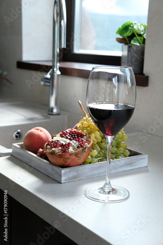 A glass of red wine and fruit the table.