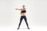 Young woman doing aerobic exercising and looking at camera