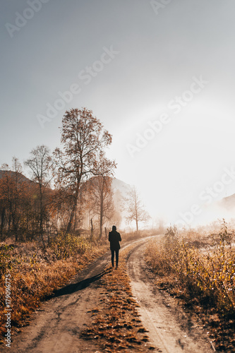 Keuken foto achterwand Europa Person walking on road in woods