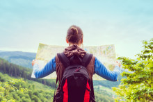 Woman Traveler With Backpack Checks Map To Find Directions In Wilderness Area, Real Explorer. Travel Concept