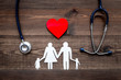 Leinwanddruck Bild - Take out health insurance for family. Stethoscope, paper heart and silhouette of family on wooden background top view
