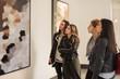 Leinwandbild Motiv Four girl friends looking at modern painting in art gallery