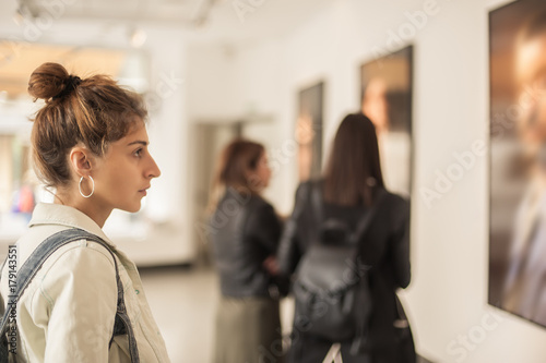 Group of woman looking at modern painting in art gallery