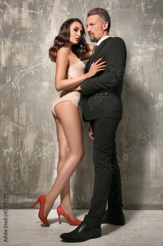 Foto op Aluminium Dance School Woman in underwear and businessman near grey wall