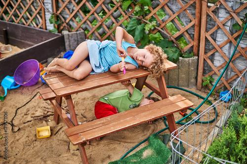 Fototapeta Mała dziewczynka leży na ławce na placu zabaw dla dzieci. obraz