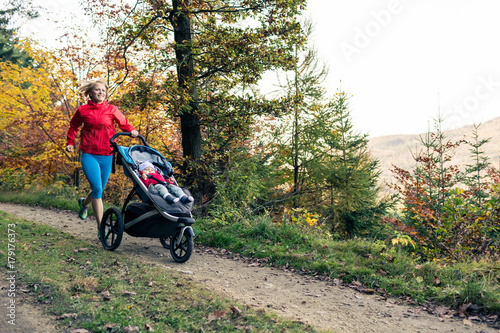 Fotografia, Obraz  Running mother with stroller enjoying motherhood at autumn sunset