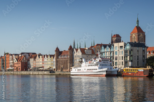View of two boats and old buildings at the Long Bridge waterfront at the Main Town in Gdansk, Poland, on a sunny day.