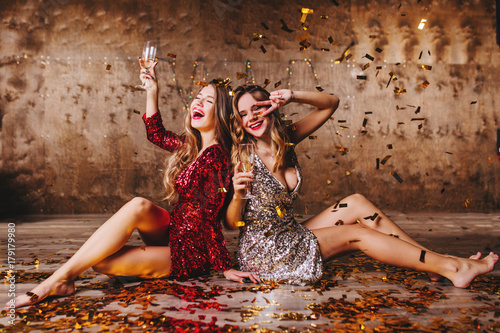 Barefooted girls drinking together after party, sitting on the ground covered with confetti. Indoor photo of laughing ladies in elegant dresses posing on the floor with wineglasses.