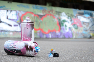 Several used spray cans with pink and white paint and caps for spraying paint...