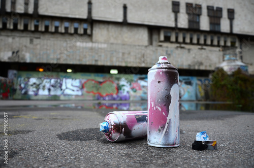Several used spray cans with pink and white paint and caps for spraying paint un Canvas Print