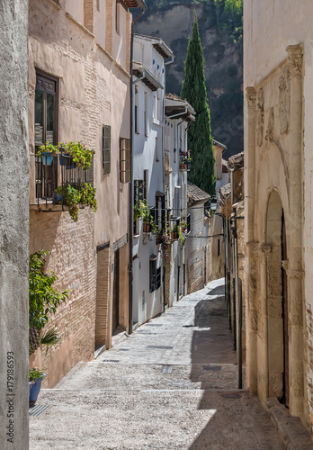 Old narrow street perspective at Albayzin district in Granada city, Spain