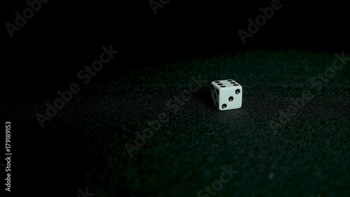 Photo  Female hand throwing dice on black background in slow motion