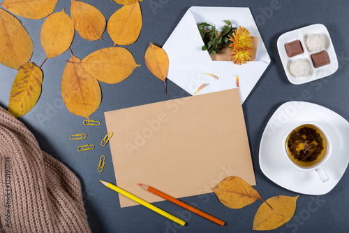 Aluminium Prints Assortment Sheet of brown craft paper, white envelope with note and flower, yellow and orange leaves, color pencils, cup of herbal tea and candies on gray background. Colorful autumn mock up. Top view.