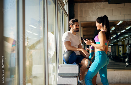 Photo Shape sporty beautiful girl flirting with a muscular guy next to her while standing near the window in the gym