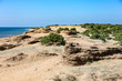 Issos - a long sandy beach - sandbar, spit - next to the Korision lake and the resort of Agios Georgios. Dunes with plants on sunny day. Mediterranean sea. Corfu, Greece.