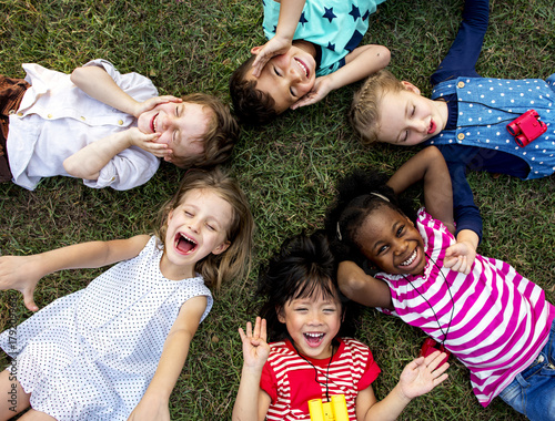 Group of kindergarten kids lying on the grass at park and relax with smiling