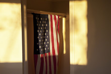 American Flag Hanging In A Closet With Setting Sun Lighting Scene