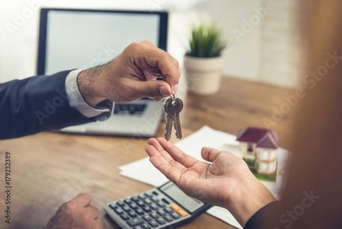 Real estate broker agent giving house keys to client Fototapet