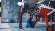 Two Mechanics Working On A Small Aircraft In A Hangar With The Cowling Off The Engine As They Perform A Service Or Repair