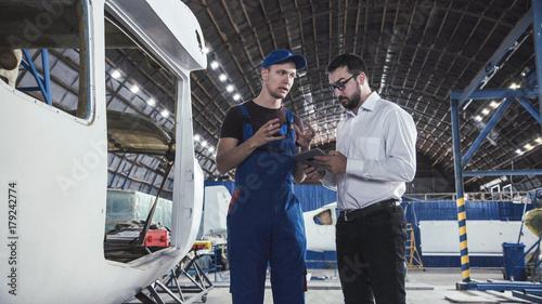 Aircraft mechanic and draftsman standing near plane carcass and talking with each other Billede på lærred