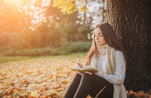 Beautiful Young Brunette Sitting On A Fallen Autumn Leaves In A Park, Reading A Book Or Write A Diary