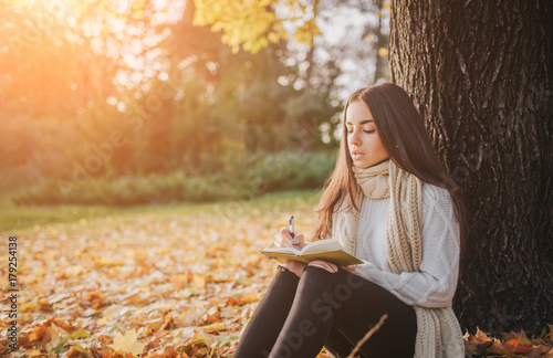 Photo Beautiful young brunette sitting on a fallen autumn leaves in a park, reading a
