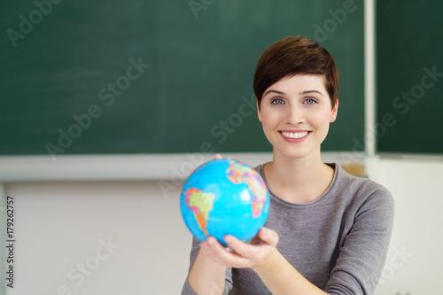 Leinwand Poster lächelnde lehrerin zeigt einen globus im unterricht