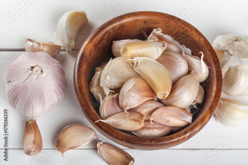 Fotobehang Schaaldieren Organic grown garlic in a wooden bowl on a white background