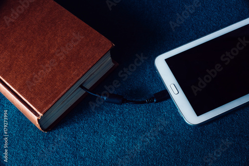 ebook reader and old book connected with cable  tablet