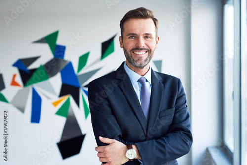 Handsome businessman in office looking at camera