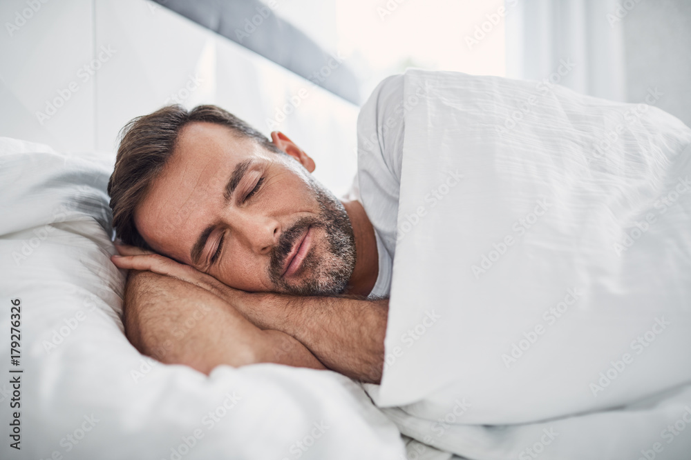 Fototapeta Peacefulness concept. Handsome man sleeping in bed