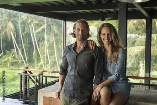 Couple smiling at camera in contemporary design house with glass facade surrounded by lush tropical garden