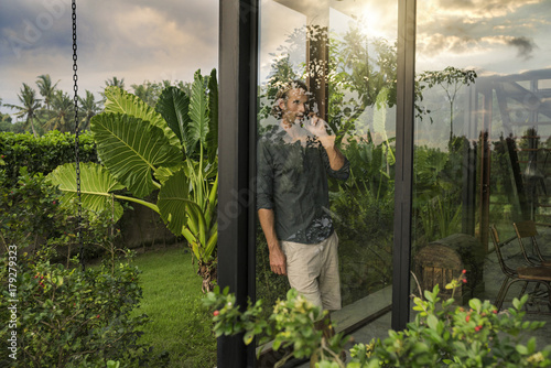 handsome man standing behind glass facade of design house talking on smartphone surrounded by lush tropical garden