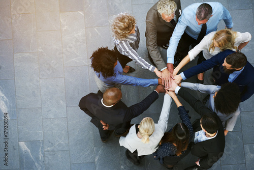 Fotografie, Obraz  United businesspeople standing in a huddle with their hands together