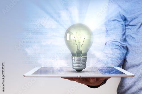 Fotografía  Mann mit Tablet, leuchtenden Glühbirne und blauen Bits