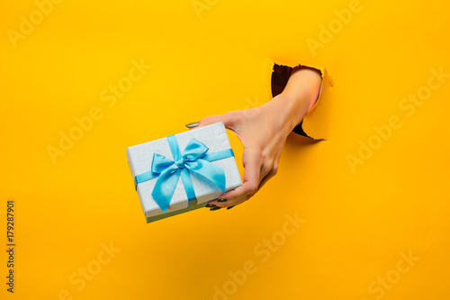 Photo  close-up of female hand holding a present through a torn paper, isolated