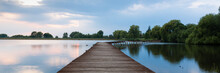 Wooden Pier, Bridge Over Lake At Dramatic Sunset With Stormy Clouds. Kuchyna, Slovakia. Panorama 3:1